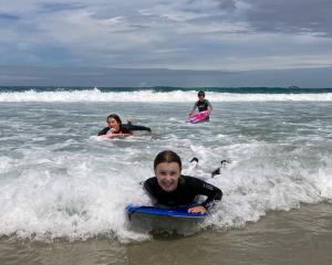 Sisters Annabel (14, left) and Isla (11) Ludgate ride the waves at St Kilda Beach. PHOTO: JACKIE...