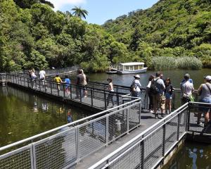 Visitors cross the lower dam on a raised boardwalk.