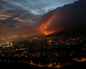 Flames are seen close to the city fanned by strong winds after a bushfire broke out on the slopes of Table Mountain in Cape Town. Photo: Reuters