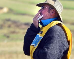 Mark Mallinson, of Geraldine, whistles for his worker.