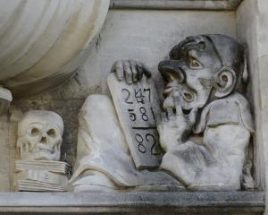 A right-hand bookend carving depicts a figure solving a mathematical sum, accompanied by a skull resting upon a pile of books, symbols of mortality and learning.