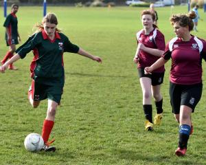 Kaikorai Valley College's Abagail Spinglio (15) looks to move the ball on while Piper McKerracher...