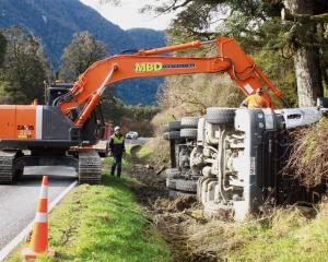 Contractors try to pull a truck back on to the road after a crash on State Highway 6 about 30km...