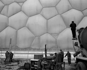 Chinese workers labour near the National Aquatics Center, also known as the Water Cube in Beijing...
