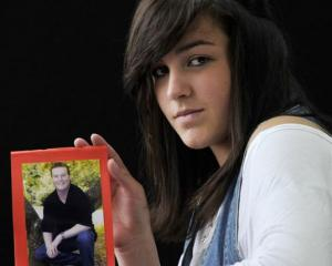 Melanoma awareness campaigner  Karli Adams (14)  holds a favourite photo of her father, Garth, ...