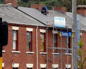A building contractor replaces a slate tile roof with corrugated iron on one of the historic...