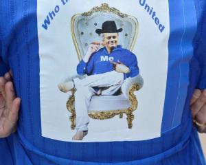A Chelsea supporter wears a shirt bearing a picture of Jose Mourinho, outside Chelsea's Stamford...
