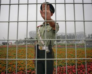 A Chinese security guard asks not to have his photo taken in front of China's National Stadium,...