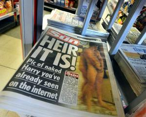 A copy of The Sun newspaper featuring a picture of a naked Prince Harry is seen in a shop in...