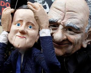 A demonstrator dressed as Rupert Murdoch holds a puppet depicting Britain's Prime Minister David...