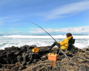 A fisher claims his patch of the Otago coast. Photo by Stephen Jaquiery.