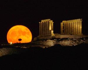 A full moon rises behind the ancient temple of Posseidon, in Sounio about 73km southeast of...