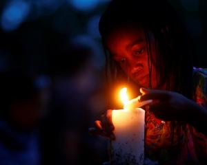 A girl lights candles outside the house where Nelson Mandela died in Johannesburg as South...