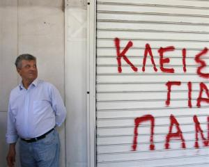 A hotel worker stands next to the shutter of a closed hotel during a protest against cutbacks and...