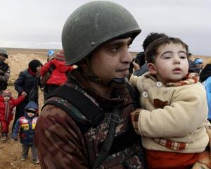 A Jordanian soldier carries a child belonging to a group of refugees who had crossed into Jordan...