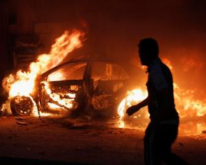 A man looks at a car on fire at the site of a bomb attack in Baghdad. REUTERS/Ahmed Saad