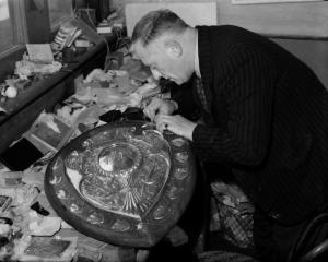 A man repairs a damaged panel on the Ranfurly Shield in this undated photograph.