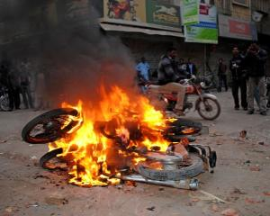 A man rides past motorbikes being burnt by supporters of Pakistan People's Party in Larkana to...