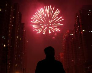 A man watches as fireworks light up the skyline of Shanghai in celebration of Chinese New Year....