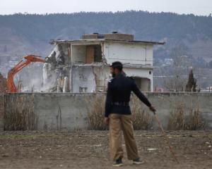A policeman looks on as the building where al Qaeda leader Osama bin Laden was killed is...