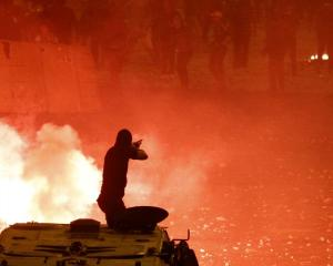 A riot police officer fires rubber bullets at Muslim Brotherhood members and Mohamed Mursi...