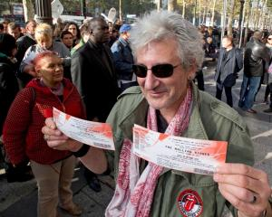 A Rolling Stones fan displays two tickets he purchased for a short warm-up gig in Paris. REUTERS...