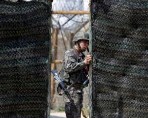 A South Korean soldier opens a gate at a checkpoint near the demilitarized zone separating North...