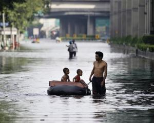 A Thai man pulls an improvised float to ferry children along flooded streets at the Lad Phrao...