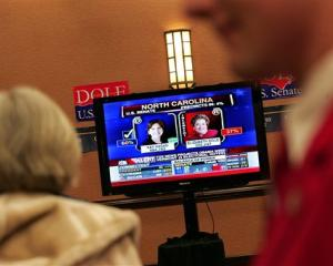 A woman watches as Fox News announces Democratic Senate candidate Kay Hagan's victory against...