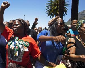 A woman with a Nelson Mandela t-shirt and badges sings and dances along with others in front of...