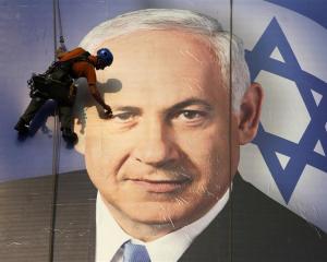 A worker installs a banner depicting Israel's Prime Minister Benjamin Netanyahu in Tel Aviv....