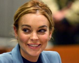 Actress Lindsay Lohan smiles during a progress report hearing at Airport Branch Courthouse in Los...