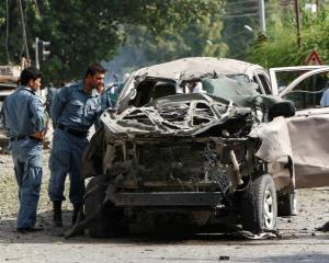 Afghan policemen inspect a vehicle hit by a bomb blast in Jalalabad province earlier this week....