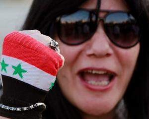 An activist wearing a glove in the colours of the Syrian flag shouts slogans against Israel...