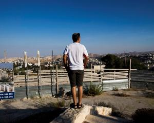 An Israeli man takes part in a ceremony announcing the resumption of construction of an Israeli...