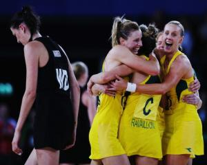 Anna Harrison of New Zealand walks off as Australia players celebrate their victory in the gold...