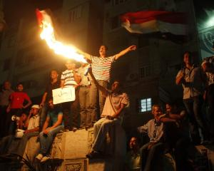 Anti-Mursi protesters light flares as they chant slogans during a second day of demonstrations in...
