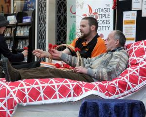 April Perkins McMillan (7) makes a donation to Otago Multiple Sclerosis field officer Don Benn ...