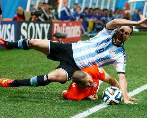 Argentina's Gonzalo Higuain (top) falls on Ron Vlaar of the Netherlands. REUTERS/Dominic Ebenbichler