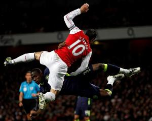 Arsenal's Robin van Persie (L) challenges Wigan Athletic's Maynor Figueroa during their Premier...