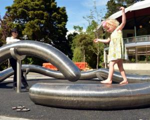 Artist Julia Morison watches Imogen Bailey (3), of Dunedin, playing on the flexible worm after...