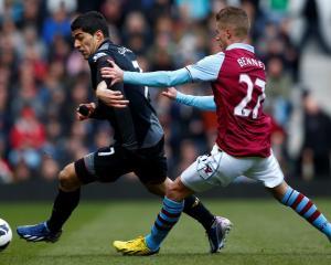 Aston Villa's Joe Bennett challenges Liverpool's Luis Suarez (L) during their English Premier...