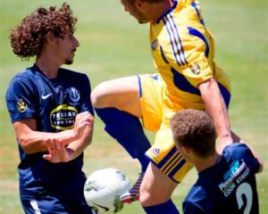 Auckland City FC's Albert Riera (left) and Simon Arms clash with Otago United's Victor Da Costa...