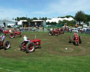 "Four pairs of vintage Farmall H tractors perform a ""tractor dance"" at the 98th West Otago A and P..."