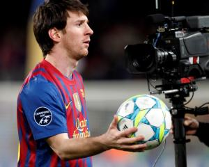 Barcelona's Lionel Messi holds a ball as he leaves the pitch after scoring five goals against...