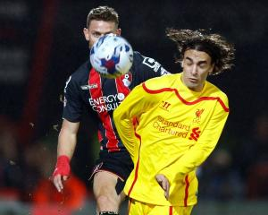 Bournemouth's Simon Francis (L) crosses the ball past Liverpool's Lazar Markovic during their...