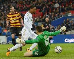 Bradford City's goalkeeper Matt Duke fouls Swansea City's Jonathan de Guzman for a penalty during...