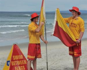 Brighton volunteer lifeguards Alex Sutherland (left) and Daniel McKay prepare flags for today's...