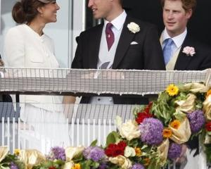 Britain's Duke and Duchess of Cambridge, left, and Prince Harry wait for the start of the Derby...