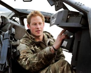 Britain's Prince Harry performs a pre-flight check on his Apache Helicopter at the British...